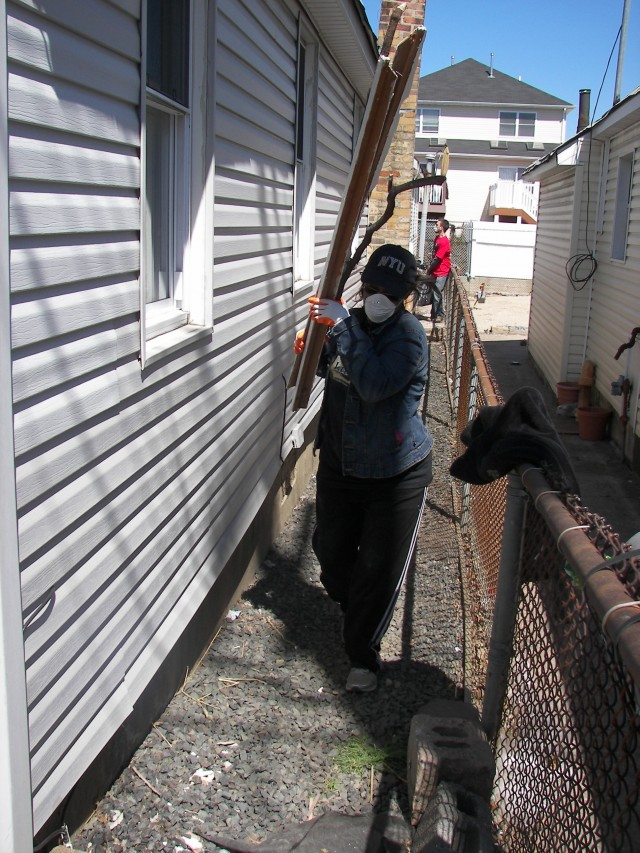 A woman wears a mask while carrying parts of a  demolished home. Photo Credit: Camilla Arellano