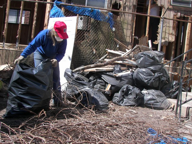 A woman picks up debris from her home. Photo Credit: Camilla Arellano
