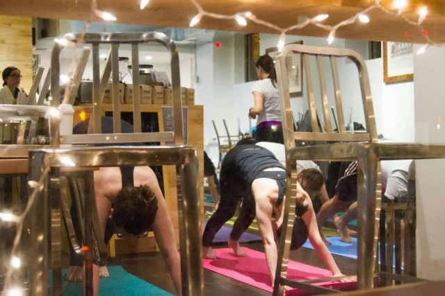 moMorgan English, 26, (right) stretching during a Pop-Up Yoga fundraiser. Photo Credit: SandyBaggers