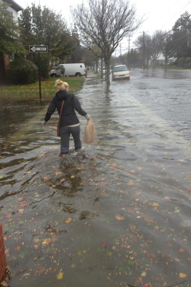 Mary-Anastasia Opperman wades through flood water in Rockaway Beach. Credit: Mary-Anastasia Opperman and Jason Rivera